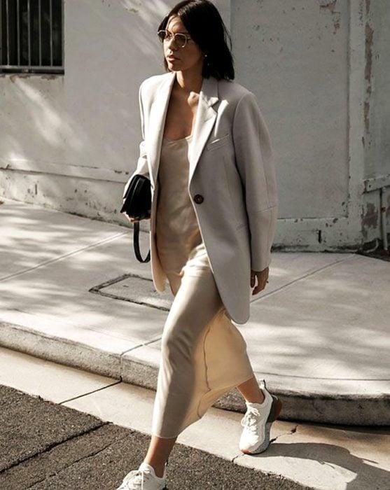 chica de cabello castaño largo usando un vestido beige claro de satén slip dress con tenis deportivos blancos, blazer oversized