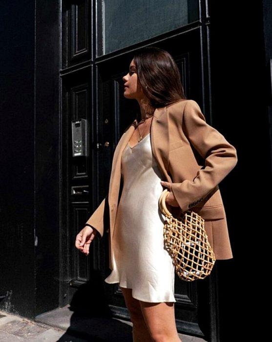 chica de cabello castaño largo usando un blazer oversized beige con vestido blanco de satén slip dress y bolso tejido