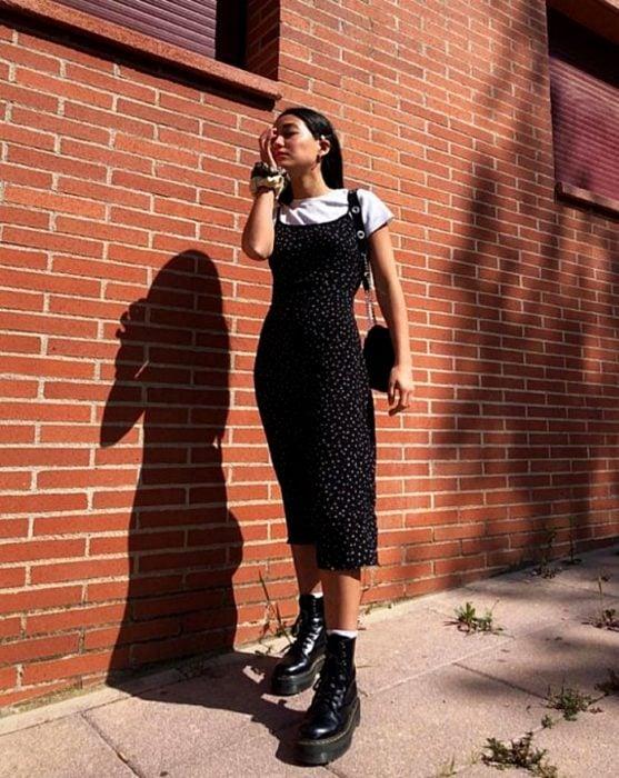 chica de cabello castaño usando un vestido negro de satén slip dress con flores, camiseta blanca de manga corta y botas de cuero negras militares y bolso de mano negro