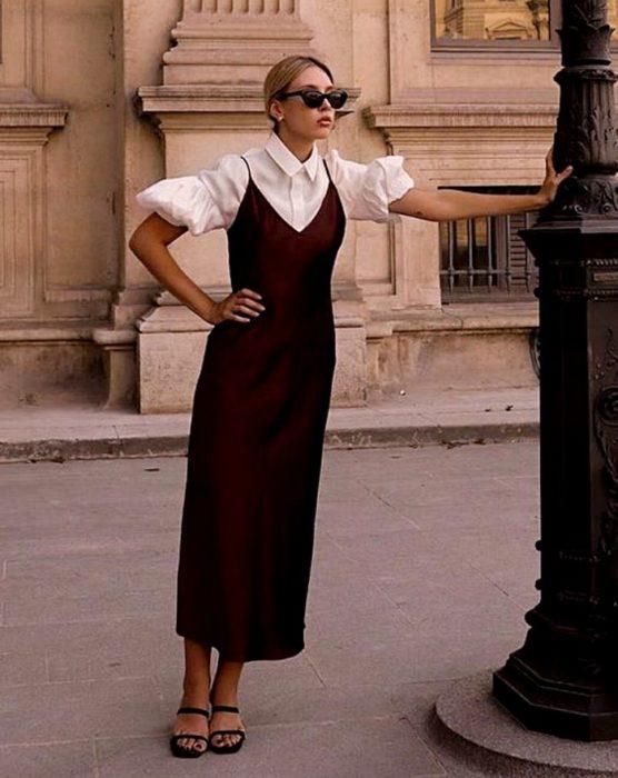 chica rubia con lentes de sol, usando una blusa blancas de mangas de globo con vestido de satén guinda y sandalias de tacón