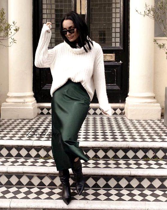 chica de cabello castaño negro usando lentes de sol, un suéter de cuello alto blanco, vestido de satén verde oscuro con botas de cuero de tacón y punta punteada