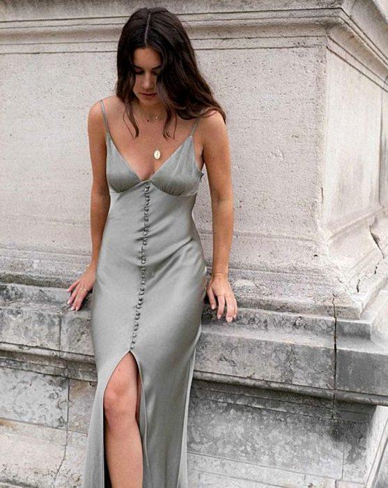 chica de cabello castaño largo usando un vestido gris de satén slip dress con botones al frente