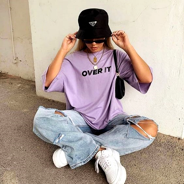 blonde girl wearing a black bucket hat, lilac T-shirt, baggy pants ripped from the knees and white tennis shoes