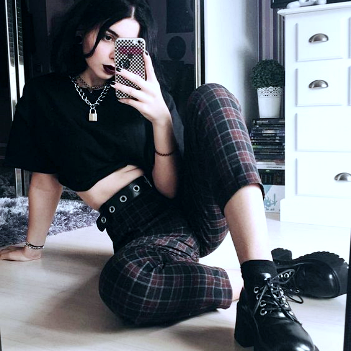 girl with black hair wearing black crop-top shirt, stud belt, black and cherry checkered pants with platform leather boots