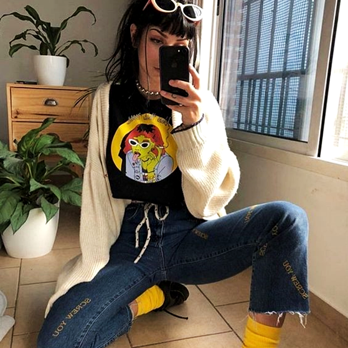 girl with dark hair wearing white sunglasses, black t-shirt with print, white cardigan sweater, flared denim pants, yellow socks and patent leather platform shoes
