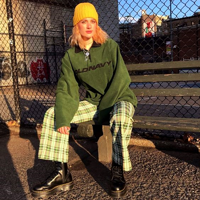 girl with pink hair wearing a yellow cap, green sweatshirt and white pants with green plaid, platform leather boots