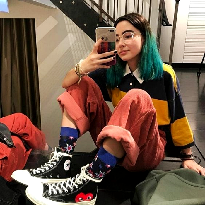 girl with blue dyed hair wearing glasses, long sleeve shirt with yellow and black stripes, pink pants, black swag converse