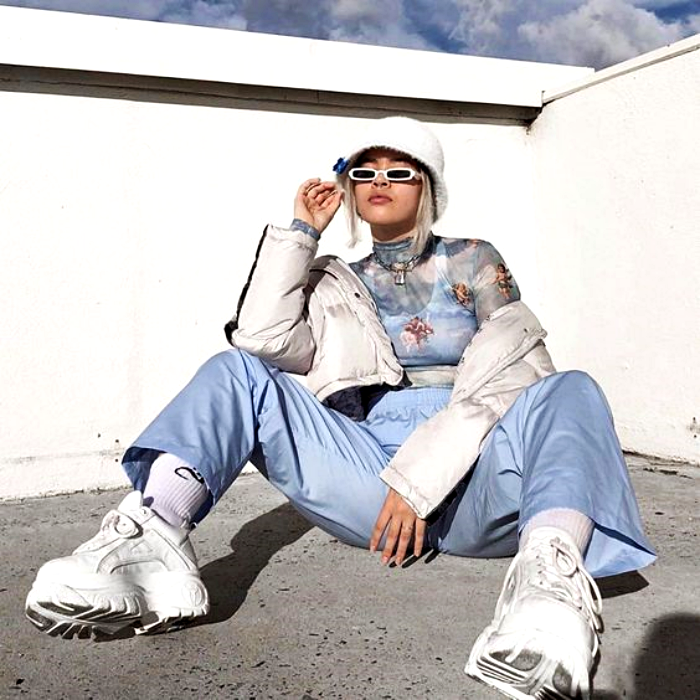 girl with platinum hair wearing a white bucket-hat, cloud print top, white jacket, light blue baggy pants and white sneakers
