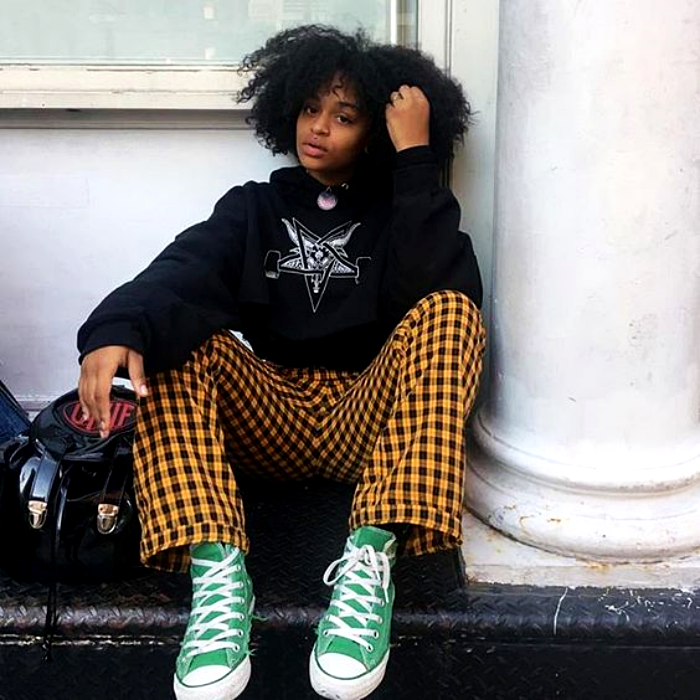 brunette girl with chinese hair wearing black patterned sweatshirt and yellow pants with black plaid, green converse