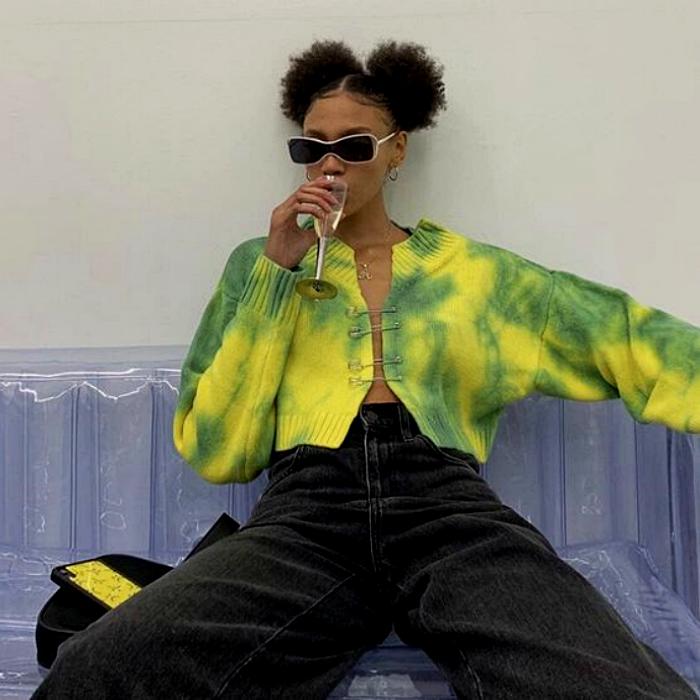 chica morena con cabello castaño usando un suéter de tie dye verde con amarillo, pantalón verde a la cintura y lentes de sol