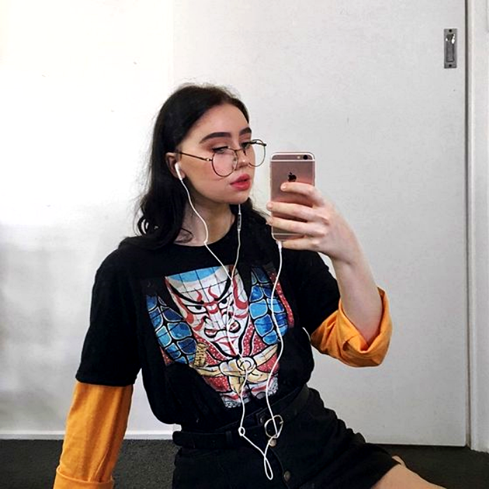 brown haired girl with glasses wearing black patterned t-shirt, orange sleeves and black mini skirt