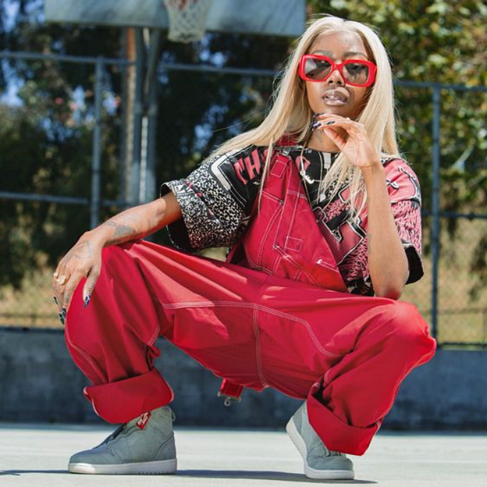 brunette girl with blonde hair wearing red sunglasses, red overall, patterned t-shirt and gray tennis shoes