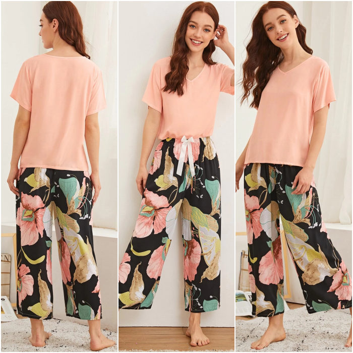 redhead girl wearing short sleeve pink t-shirt pajamas, black baggy pants with large flower print