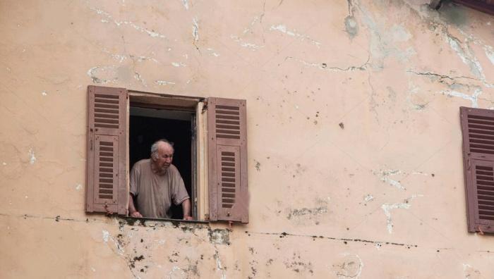 señor en italia viendo por la ventana imagen de stock