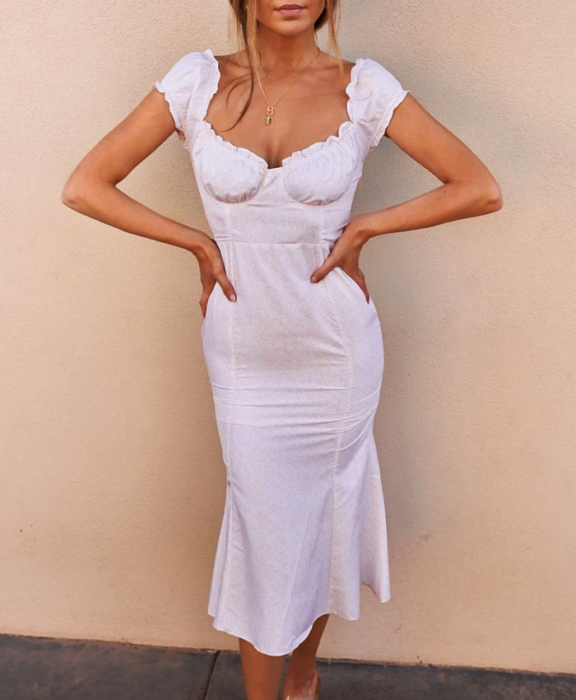 girl with her hair up wearing a tight white dress with thick straps and neckline