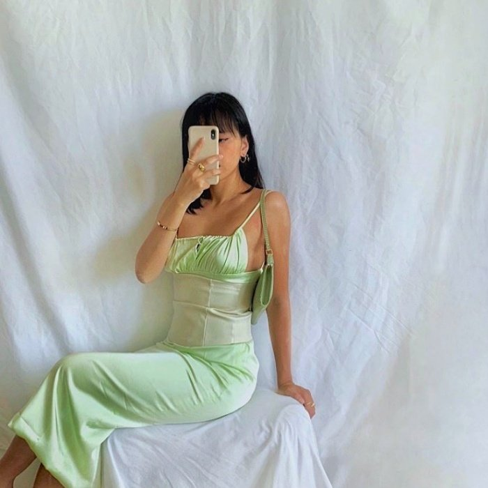 brown haired girl wearing pastel green satin dress with white corset