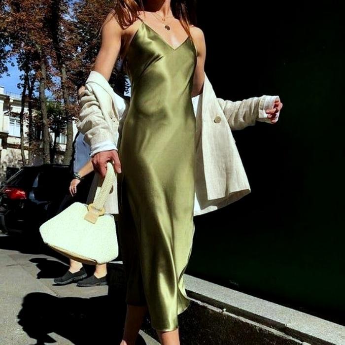 girl wearing v-neck green satin dress and white cardigan, white handbag