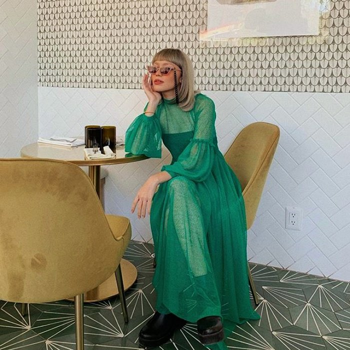 short platinum hair girl wearing pink sunglasses, green dress with long sleeves tulle, black boots