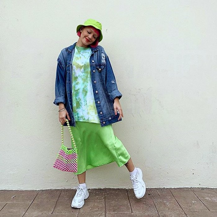 girl wearing a green bucket hat with denim jacket, green tie-dye t-shirt and green satin dress with pink bag and sneakers