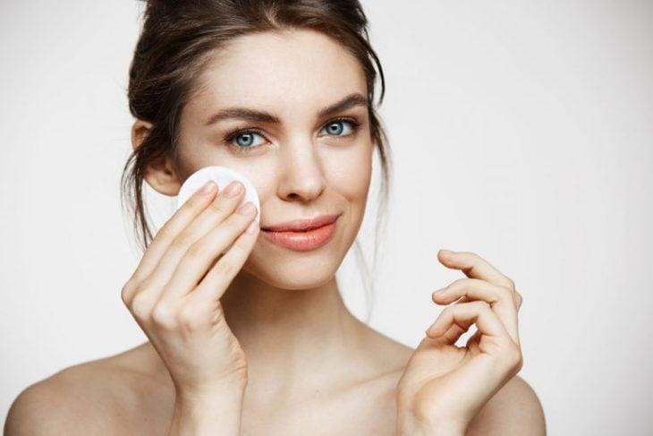 Chica limpiando su rostro con un pad de algodón