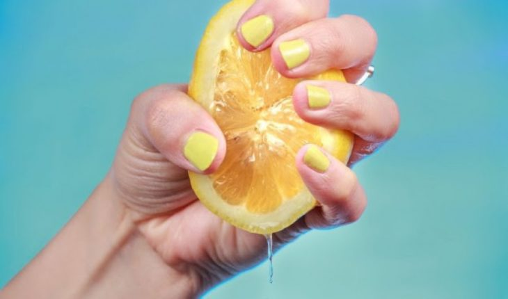 Mano de una chica apretando la mitad de un limón