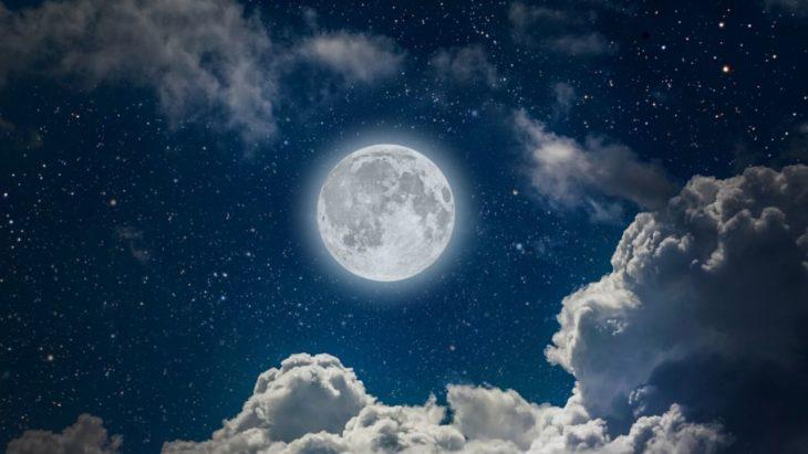 Luna llena con aura azul en cielo con nubes