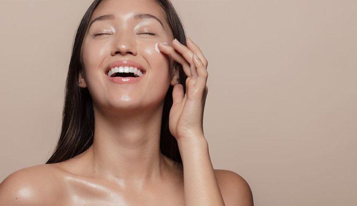 Chica aplicándose crema en el rostro