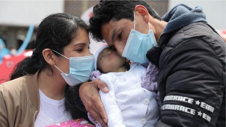 Diana y su esposo abrazando a su bebé después de ser dadas de alta del hospital