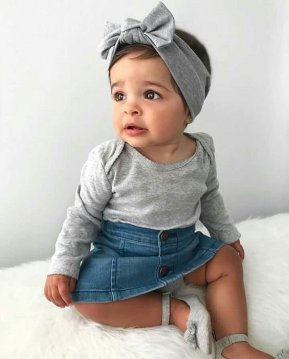 Bebé usando blusita gris, con faldita y diadema