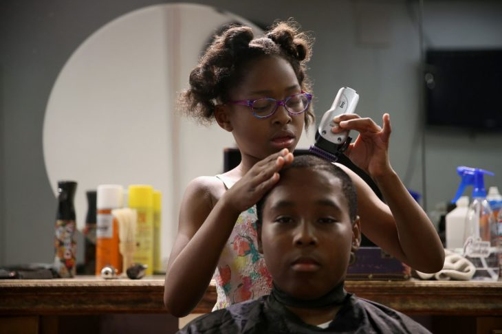 Neijae Graham-Henries cortandole el cabello a un niño
