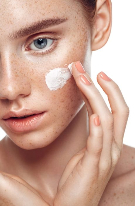Chica aplicándose crema en la cara