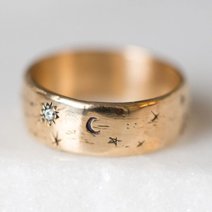Golden ring with carved details of stars, moon and suns