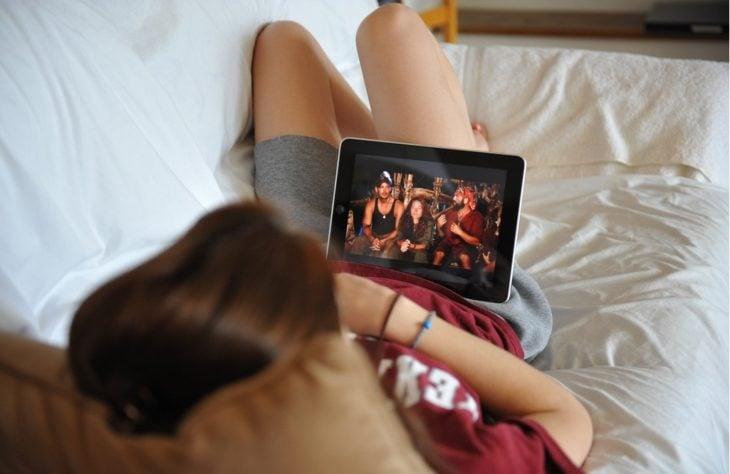 Chica viendo series recostada en el sofá
