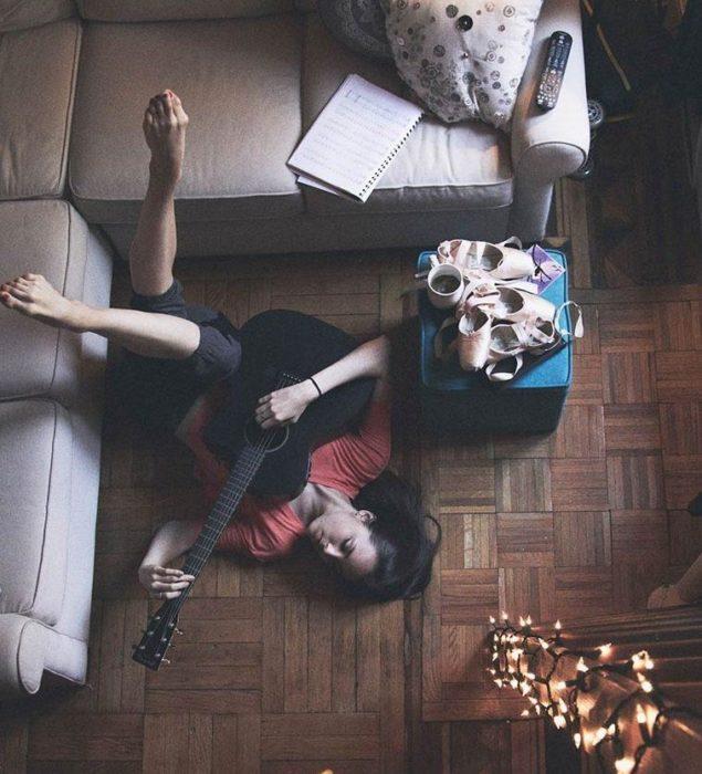 Chica tocando guitarra en su casa