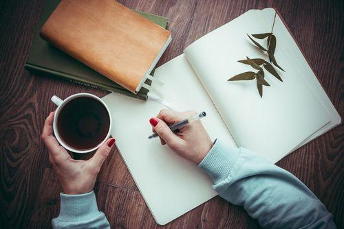Mujer escribiendo en una hoja en blanco