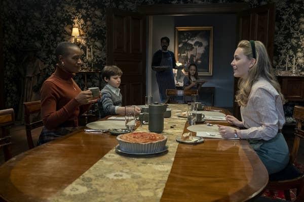 Escena de la serie La maldición de Bly Manor, familia sentada en un comedor