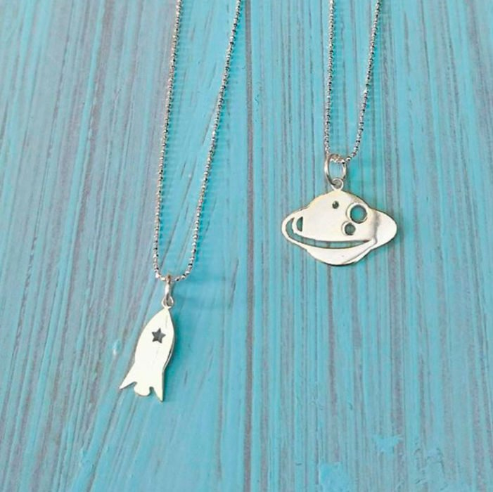Necklaces in silver color in the shape of Saturn and spaceship