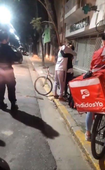 Joven repartidor abrazando a la chica que le regaló su bicicleta después de que le le robaran la suya