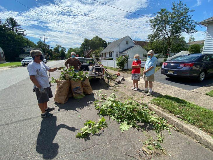 Brian Schwartz recogiendo ramas después de un trabajo de jardineria