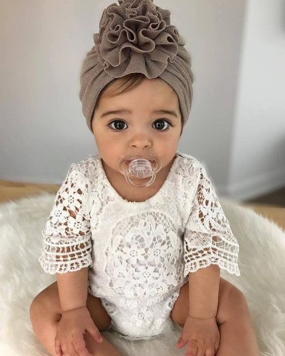 Bebé usando blusa blanca y diadema