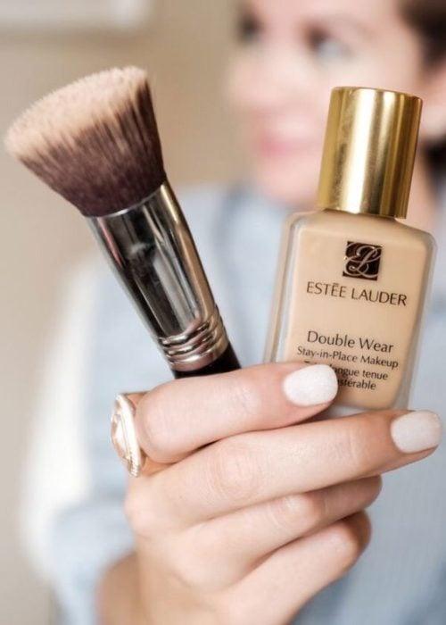Chica sosteniendo una base de maquillaje y una brocha con su mano