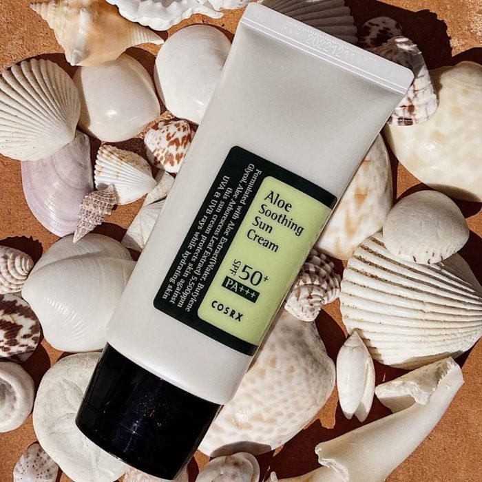 Container of sunscreen on sea shells
