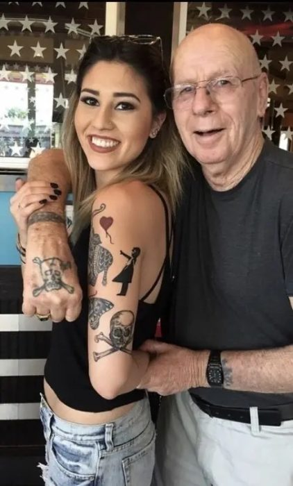 Grandpa and his granddaughter showing their matching tattoos