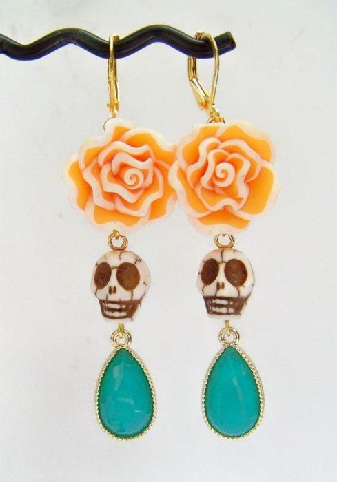 Accesorio inspirado en Día de muertos de aretes de calavera, con una gema en la parte inferior y una flor de sempasuchil en la parte superior