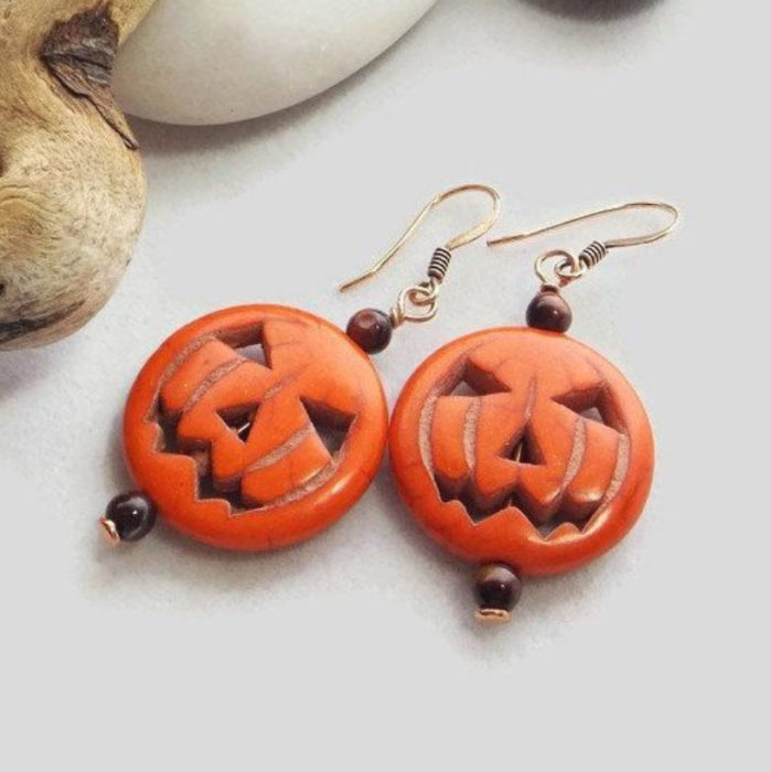 Halloween-inspired accessory of pumpkin earrings with faces