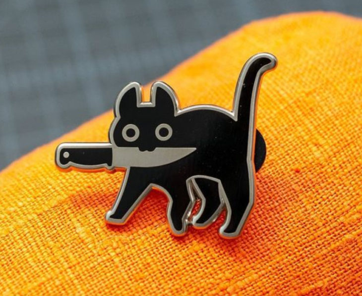 Halloween-inspired accessory of a black kitty pin with a knife