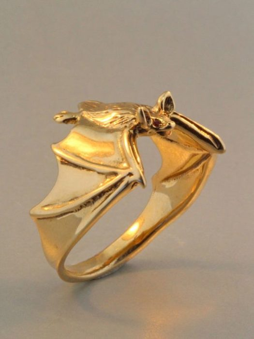 Halloween inspired accessory of a gold ring of a bat hugging the finger