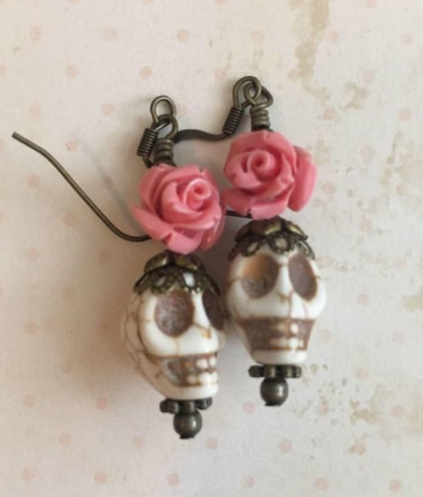 Day of the dead inspired accessory of beige skulls with a pink rose on top