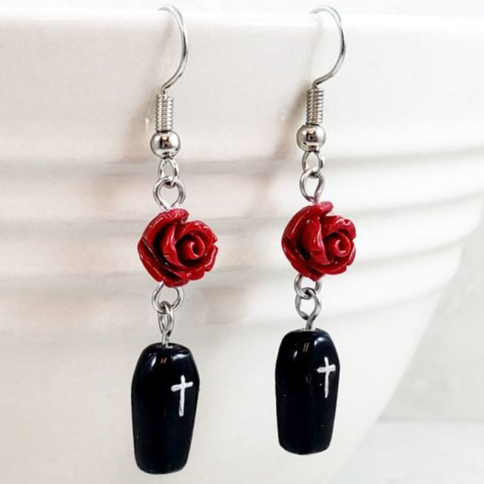 Halloween-inspired accessory of earrings with a red rose and coffin on the bottom