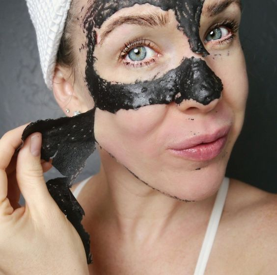Girl removing a charcoal mask from her face